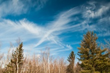 "High cirrus clouds create a broad ""X"" in a blue sky on Sunday afternoon."