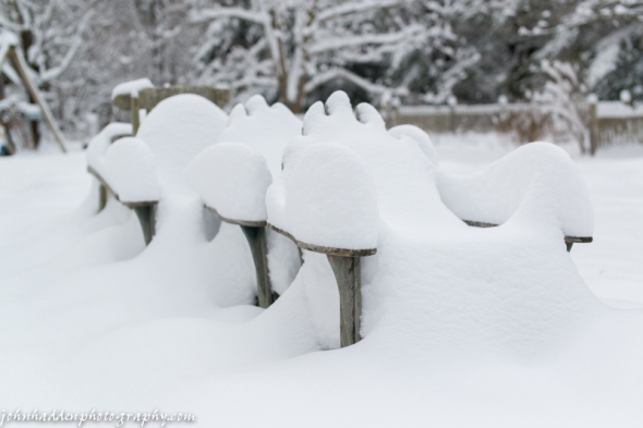 Adirondack chairs piled with snow by the volleyball court