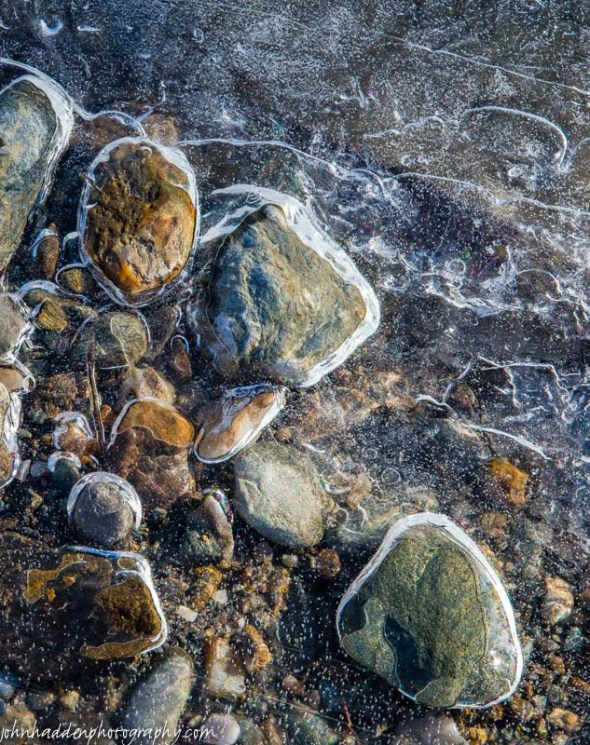 Stones and pebbles held in clear ice in Fargo Brook
